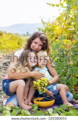 A cute happy family mother and two happy childrens friends outdoor are holding bunch of grapes in autumn vineyard