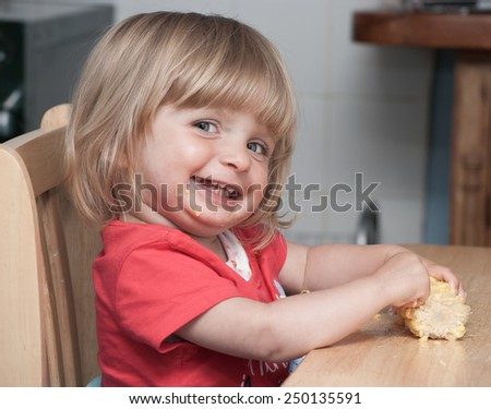 A cute happy smiling baby eating Corn at the table.  - stock photo