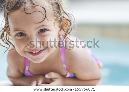 A cute happy young female girl child baby relaxing on the side of a swimming pool  - stock photo