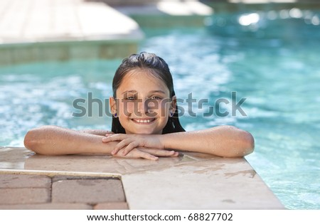 A cute happy young girl child relaxing and smiling on the side of a swimming pool - stock photo