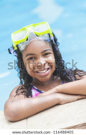 A cute happy young interracial African American girl child relaxing on the side of a swimming pool smiling & wearing pink goggles - stock photo