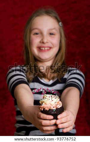a cute kid eating a fresh baked cupcake with colorful frosting. - stock photo