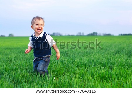 A cute little baby boy sit in the grass - stock photo