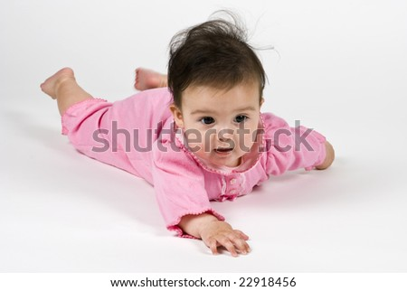 A cute little baby girl dressed in a pink outfit laying on a white backdrop.