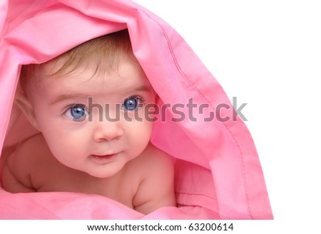 A cute little baby girl is staring up and is hiding under a pink sheet blanket. She is isolated on a white background. Add your text to the right side. Use it for a child, parenting or love concept. - stock photo