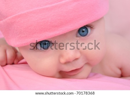 A cute little baby girl is staring up and is on a pink blanket. She is wearing a pink hat and has big blue eyes. Use it for a child, parenting or love concept.