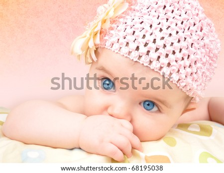 A cute little baby girl is wearing a flower hat and sucking her thumb. There is a pink background.