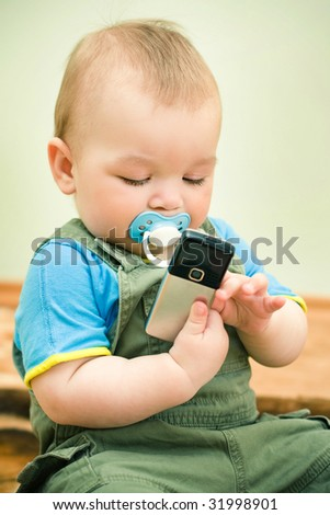 A cute little baby girl playing with a cell phone - stock photo