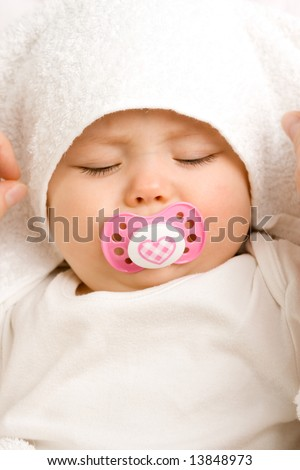 A cute little baby girl sleeping with a dummy in her mouth. - stock photo