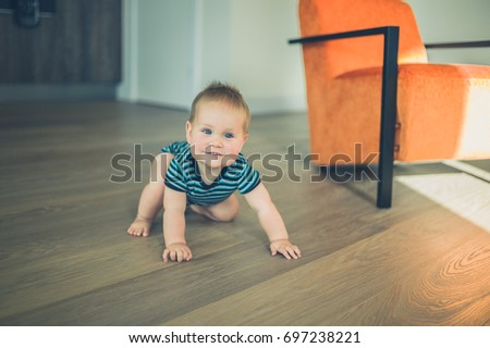 A cute little baby is crawling around a modern apartment in the sunlight
