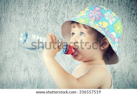 A cute little baby is drinking water from a bottle - stock photo
