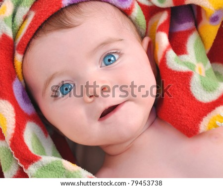 A cute little baby is laying in a bed with a bright red blanket around their face.