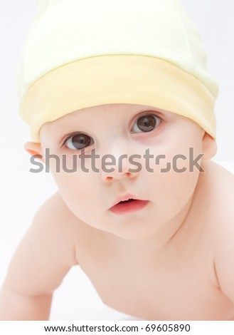 A cute little baby is looking into the camera - stock photo