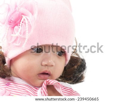 A cute little baby is looking into the camera and is wearing a pink hat - stock photo