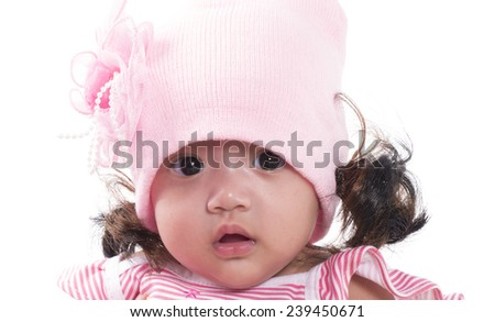 A cute little baby is looking into the camera and is wearing a pink hat