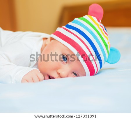 A cute little baby is looking into the camera and is wearing a white hat. The baby could be a boy or girl and has blue eyes. use it for a parenting or love concept. - stock photo