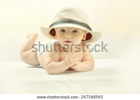A cute little baby is looking into the camera and is wearing a white hat. The baby could be a boy or girl - stock photo
