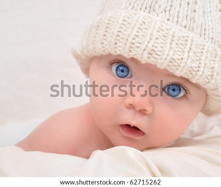 A cute little baby is looking into the camera and is wearing a white hat. The baby could be a boy or girl and has blue eyes. use it for a parenting or love concept.
