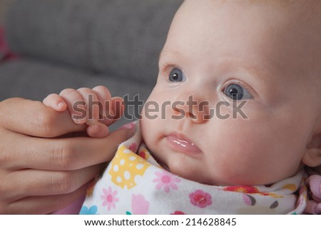 A cute little baby is looking straight to her mom - stock photo