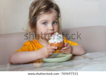 A cute little baby is sitting at a table eating a bun. Child with blue eyes