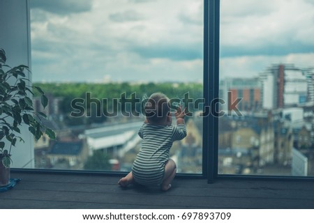 A cute little baby is sitting on a balcony in a high rise apartment block in the city