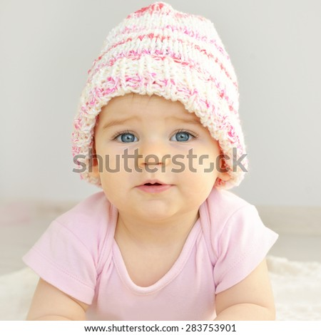 A cute little baby. Newborn baby girl in pink knitted hat. Parenting or love concept. - stock photo