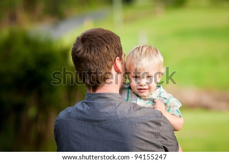 A cute little blond haired, blue eyed boy plays with his Dad in an outdoor field - stock photo