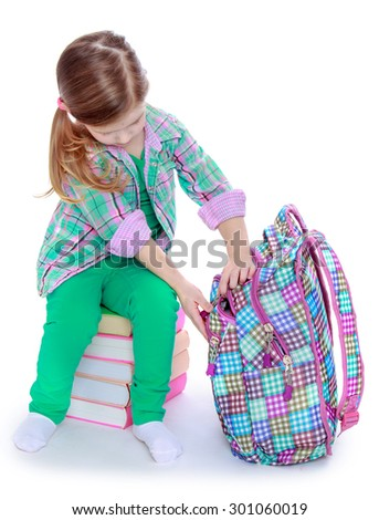 A cute little blonde girl with the long ponytail on her head sitting on a pile of books. Girl puts books in school bag that closes with a zipper. The girl is going to go to 1 class-Isolated on white - stock photo