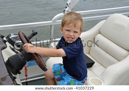 a cute little boy drives a boat - stock photo
