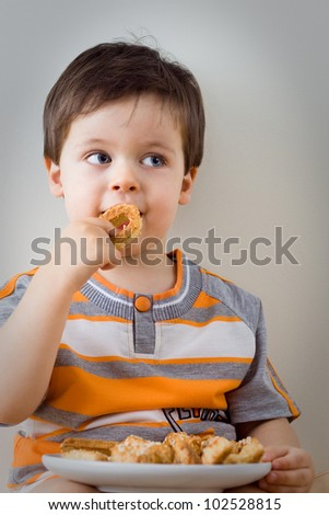 A cute little boy eats a homemade cookie indoors - stock photo