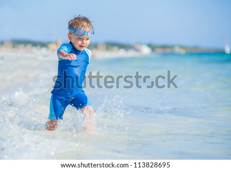 A cute little boy having fun on the exotic beach - stock photo