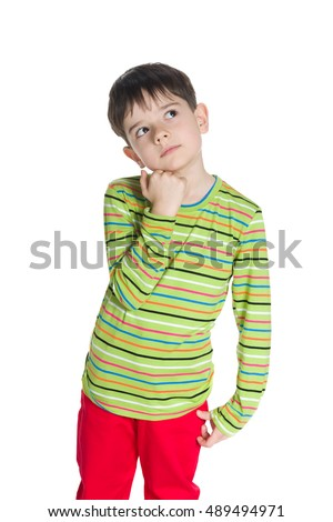 A cute little boy in a green striped shirt looks up