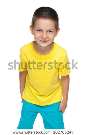 A cute little boy in the yellow shirt stands against the white background