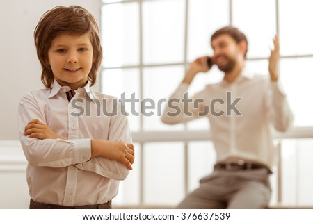 A cute little boy in white classical shirt looking in camera and smiling, in the background his father talking on the phone. - stock photo