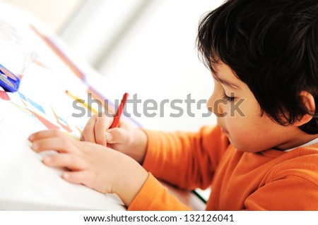 A cute little boy is drawing and being creative