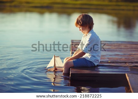 A cute little boy sitting on the pontoon bridge on the river with a toy ship in hands in a warm sunny summer day. Water and boat. - stock photo