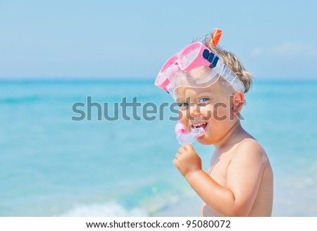 A cute little boy wearing a mask for diving background of the sea - stock photo