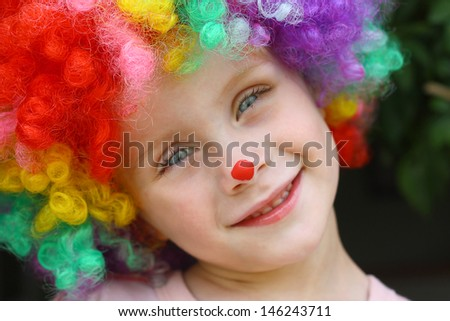 a cute little child dressed up in a clown costume and face paint and smiling - stock photo
