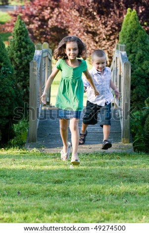 A cute little children running happily over a wooden bridge through the park.  Shallow depth of field. - stock photo