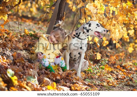 A cute little girl and her dalmatian outdoor during autumn - stock photo