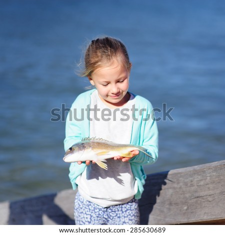 A cute little girl holding a fish with the sea water in the background, focus on the fish - stock photo