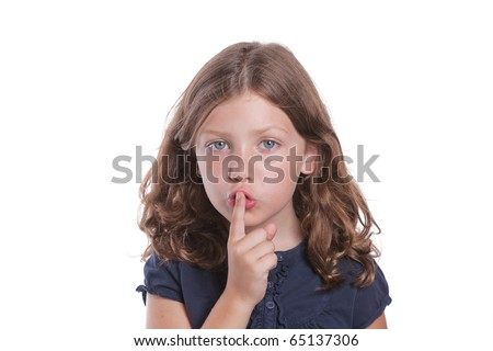 A cute little girl holds her finger over her mouth to shush - stock photo