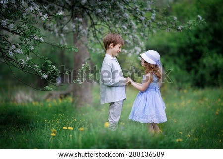 A cute little girl in an elegant white hat and light blue dress and a cute young boy embracing in the blooming garden on a sunny spring day. Kids in the country.  - stock photo