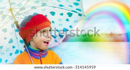 A cute little girl looks admiringly at the rainbow - stock photo
