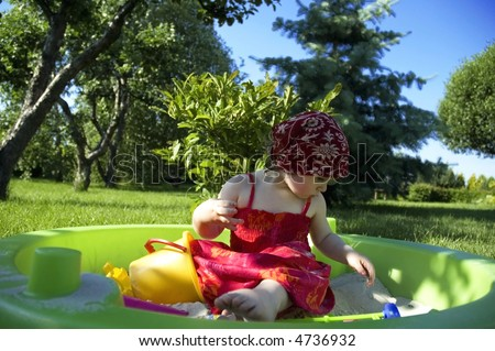 a cute little girl playing in the garden - stock photo