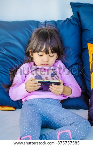 A cute little girl playing smart phone and laying on white couch in living room with big blue pillows