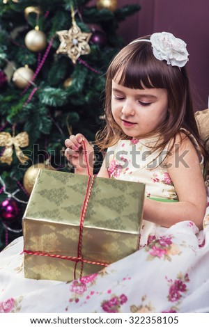 A cute little girl princess thoughtfully opening a gift in gold packaging. Merry Christmas and happy New Year! A series of photos