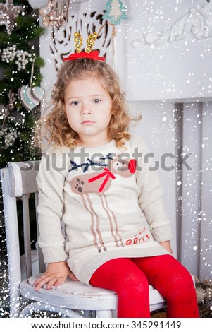 A cute little girl sits with a gift  on a chair near a fire-place. Christmas sceneries.