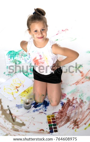 A cute little girl smiles and draws paints and brushes. The concept of happiness, family, child, childhood, art training. Isolated over white background