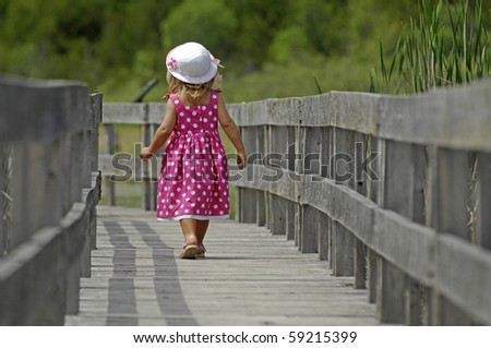 A cute little girl takes a stroll on the boardwalk through the marsh.